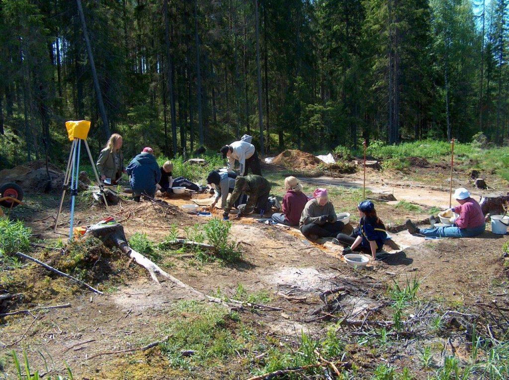 Ihmisiä kaivauksella aurinkoisena päivänä.