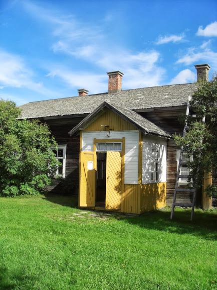 Harmaa talo, jonka eteinen on maalattu keltaisella ja valkealla. Ovi on auki.