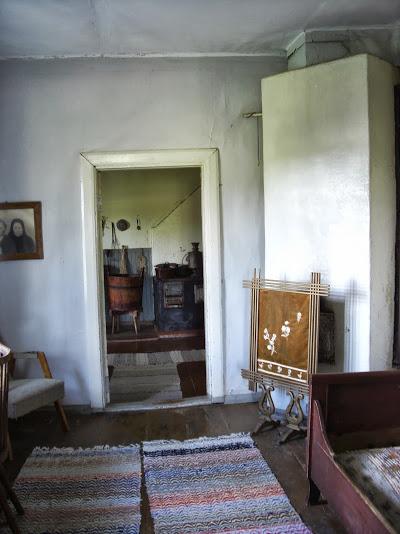 Vanhoja huonekaluja harmaassa huoneessa. Huoneen nurkassa uuni, seinällä taulu ja lattialla mattoja. Ovesta näkymä seuraavaan huoneeseen.