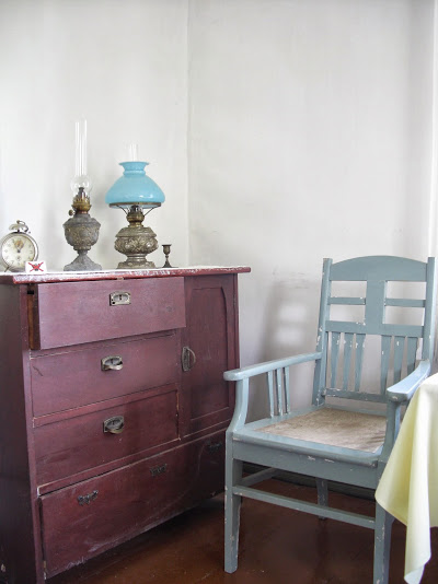 Punainen lipasto, jonka päällä herätyskello ja lamppuja. Lipaston vieressä harmaaksi maalattu tuoli.