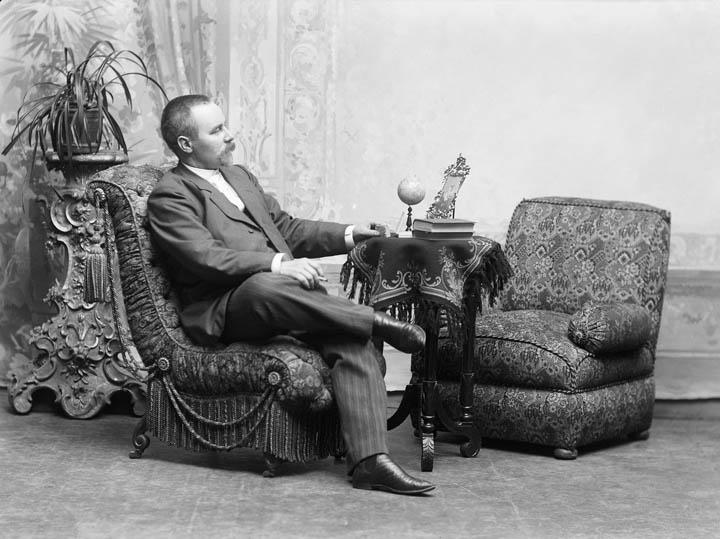 Victor Barsokevitsch nojatuolissa. Pöydällä kirjoja ja pieni maapallo. Takana ruukkukukka jalustalla.