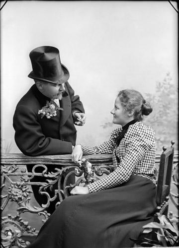 Victor nojautuu aidan ylitse silinterihattupäässään ja sikari kädessään. Irene istuu aidan toisella puolella. Katseet kohtaavat.