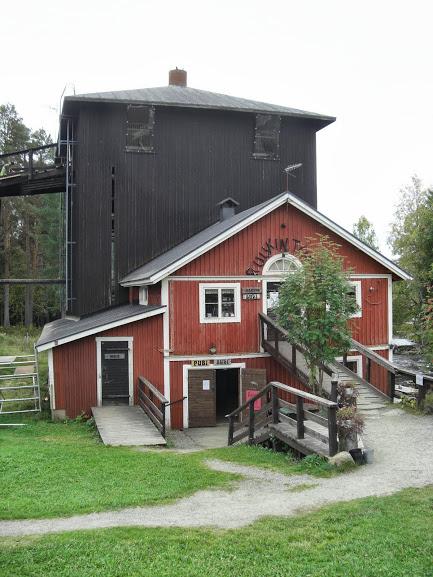 Punainen puinen ruukkirakennus, johon silta yläkertaan ja portaat alakertaan. Taustalla mustaksi maalattu osa.
