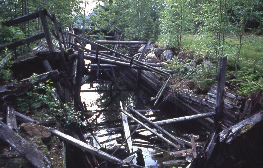 Vanha kanava, jonka rakenteet ovat alkaneet sortua. Kanavassa kulkee vettä ja sen ympäristö on metsittynyt.
