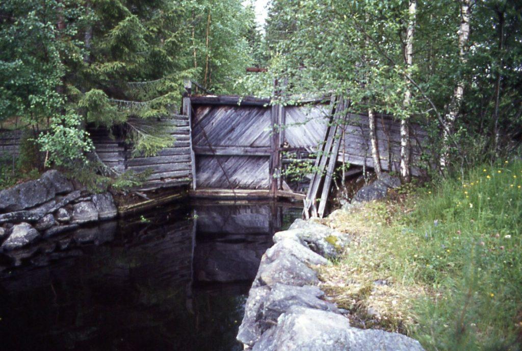 Kanavan portti on taipunut sisäänpäin. Kanavassa kulkee vettä, mutta ympäristö on metsittynyt.