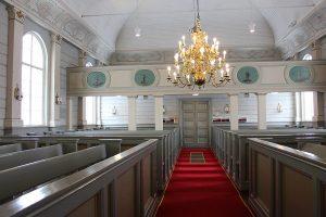 Näkymä kirkon sisältä. Kattokruunu, punainen matto, puiset penkkirivit ja suuret ikkunat.