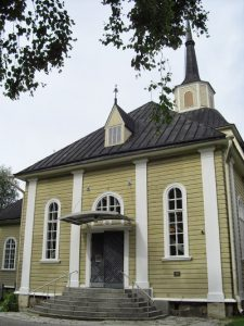 Kirkon sisäänkäynti, portaat vievät mustalle ovelle.