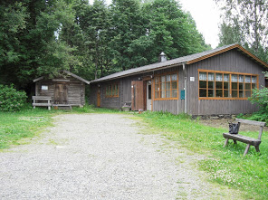 Hiekkatien varressa puinen penkki. Tien päässä harmaa puutalo ja sen pihassa pieni harmaa aitta tai varasto. Ovi auki taloon. Talon takana puita.