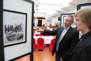 Mies osoittaa mustavalkoista seinälle ripustettua kuvaa. Toinen mies katsoo vieressä.