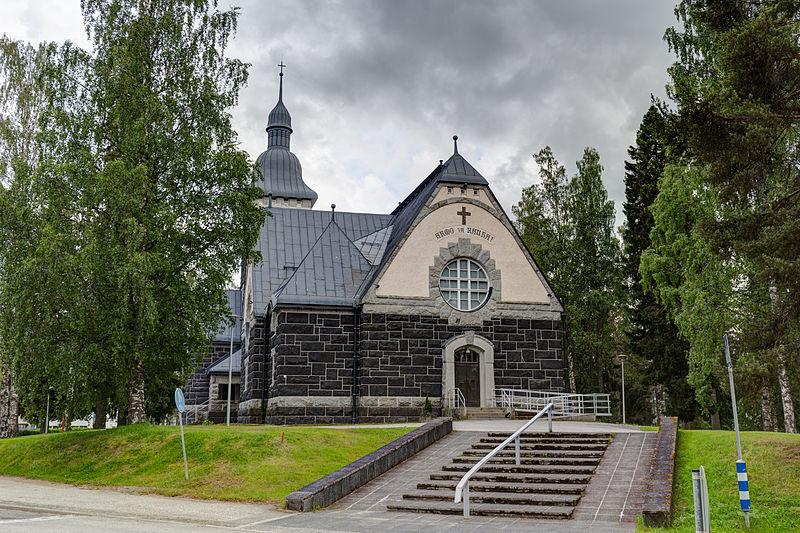 Tummasta kivestä tehdyn kirkon yläosa vaalean ruskeaa. Päädyssä pyöreä ikkuna. Kuvan etualalla loivat rappuset vievät päätyovelle.