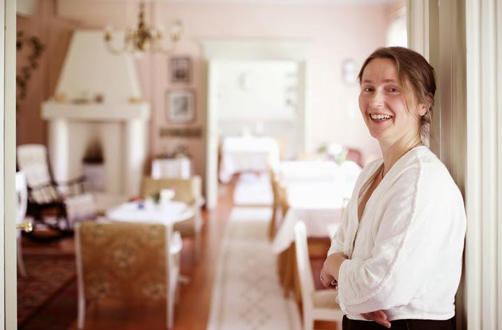 Nainen nojaa ovenkarmiin. Taustalla vanhalla tyylillä sisustettu vaaleanpunainen huone.