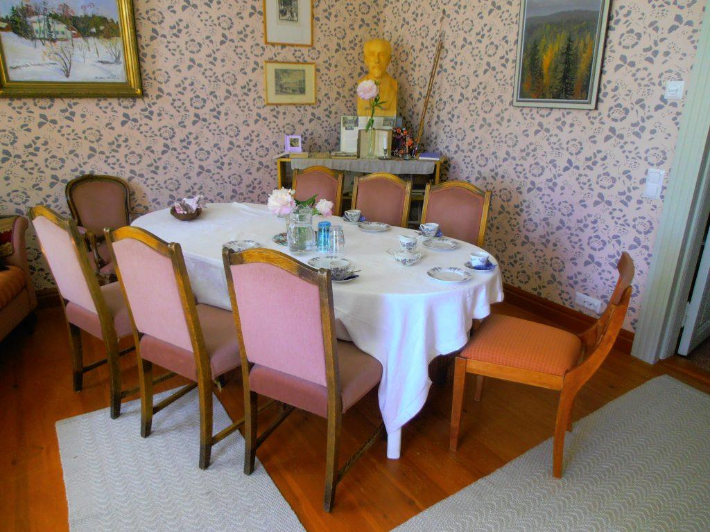 Huoneessa ovaalin muotoinen pöytä, jonka ympärillä kahdeksan tuolia. Tuoleissa vaaleanpunainen verhoilu. Seinällä vaaleanpunaiset kukkakuviolliset tapetit ja tauluja.
