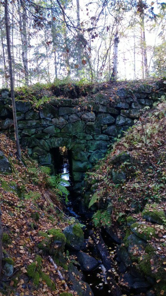 Luonnonkivistä rakennettu silta. Keskellä kapea, ylhäältä pyöreä aukko, josta vesi pääsee läpi. Ympärillä kivet ovat sammaloituneet.
